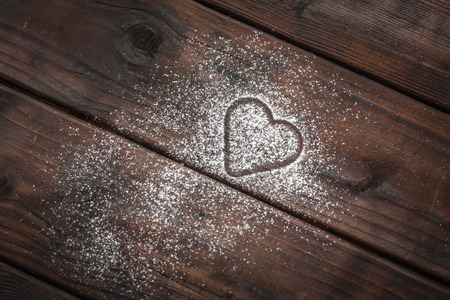 powdered: shape of a heart with powdered sugar on wooden background