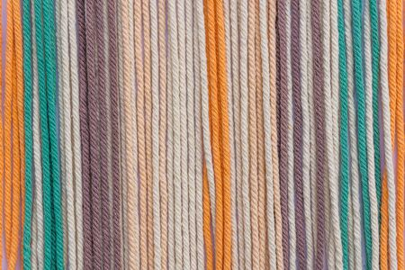 Colorful macrame threads texture closeup for background.