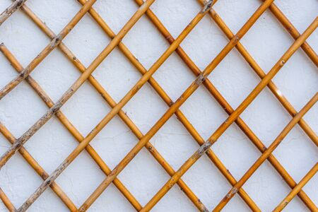 Grid of wooden fence against old white wall background. Closeup.
