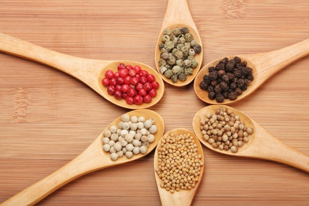 Colorful spices in wooden spoons - beautiful kitchen image. black, red green and white pepper, coriander, mustard photo
