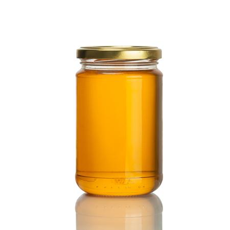 frasco: tarro de miel de abeja en el fondo blanco, aislado Foto de archivo