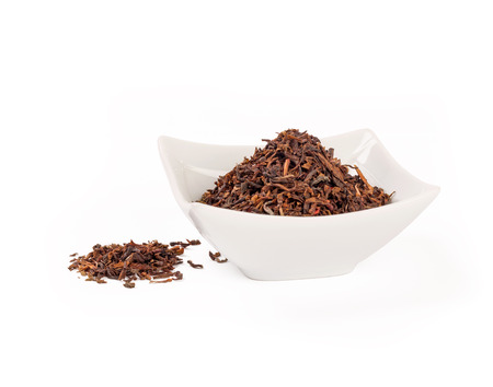 loose leaf: Heap of red rooibos healthy traditional organic tea on white isolated background.