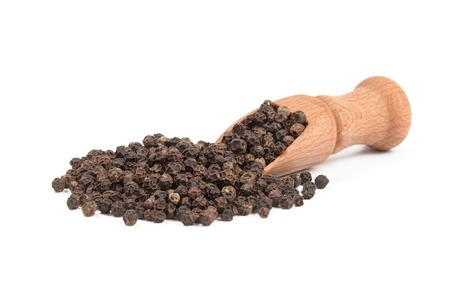 Black pepper in a wooden spoon isolated on the white background