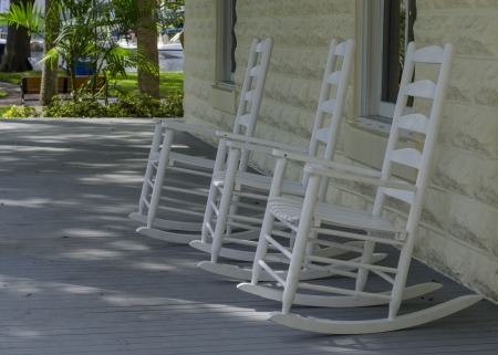 three rocking chairs on a front porch photo