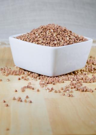 raw buckwheat groats known as kasha in a ceramic bowl Zdjęcie Seryjne