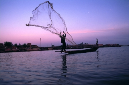 fisherman on boat: throwing fishing net at sunrise