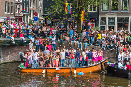 Amsterdam, August 5 2017: Visitors watching the Boats of the 2017 Canal parade sailing over the canals of the Prinsengracht in the center of Amsterdam Editorial