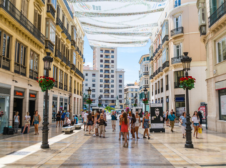 Malaga, Spain, June 27, 2017: Tourists shopping at the Calle Marqués de Larios