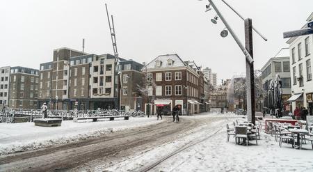 Den Bosch, The Netherlands, December 10th 2017: People crossing the snow covered visstraat in the center of Den Bosch