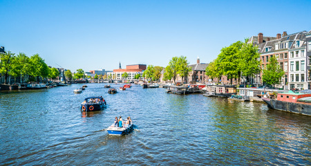 Amsterdam, May 7 2018 - view on the river Amstel filled with small boats and the Stopera (opera building) in the background on a summer day Editöryel