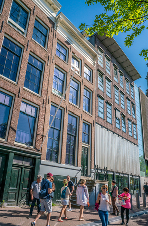 Amsterdam, May 7 2018 - Touriust passing the famous house of Anne Frank at the PRinsengracht