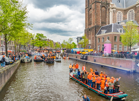 Amsterdam, The Netherlands, April 27 2018, Tourists and locals sailing on the Prinsengracht in front of the Westertoren to celebrate Kingsday Redactioneel