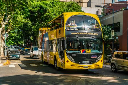 Yellow Double decker Tourists bus filled with tourists visiting Recoleta, Buenos Aires, Argentina - January 23th 2019