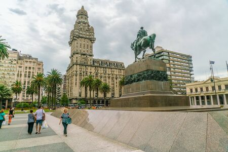 Tourists passing the statue of General Artigas on the Independance square (Plaza Indepencia) with in the background the famous Salvo Palace (Palacio Salvo), Montevideo, Uruguay, January 25th 2019