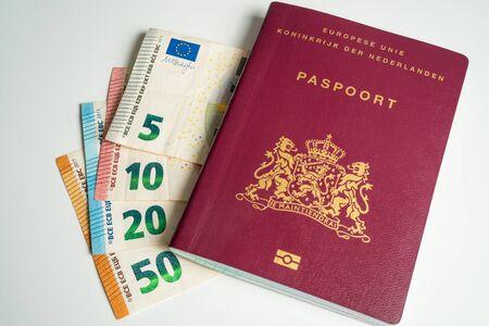 Dutch passport with Euros next to it. Five, ten, twenty and fifty Euros Фото со стока