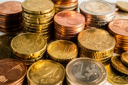 Several Euro coins stacked per value. Twenty, ten and five, one and two euros