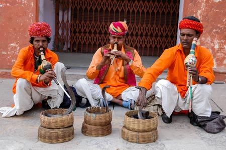 serpiente cobra: Agra, India, 24 de abril de 2007 - encantadores de serpientes no identificados en la calle de Agra, India. Encantadores de serpientes que fingen hipnotizar a una serpiente por tocar un instrumento llamado Pungi
