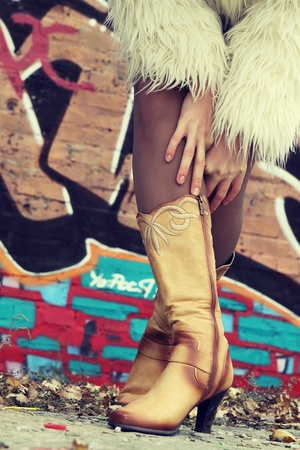 vandalize: womanish knee-boots and hands on a background a wall with grafiti