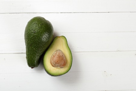 hass: Avocado on a board painted with white paint Stock Photo