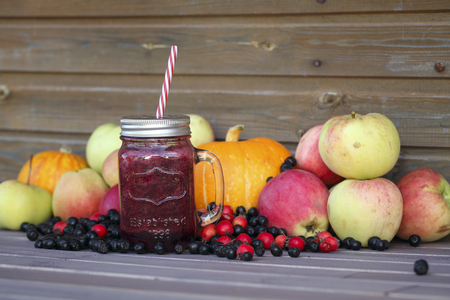 harvest festival: Berry smoothie on rustic wooden background. Autumn Harvest Festival