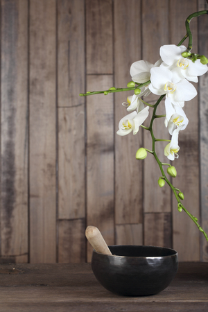 singing bowl massage: Flowers white orchid on a dark wooden background close-up. The shape of the frame. Tibetian singing bowl Stock Photo