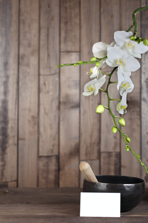 singing bowl: Flowers white orchid on a dark wooden background close-up. The shape of the frame whith card for letters. Tibetian singing bowl