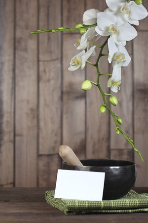 singing bowl massage: Flowers white orchid on a dark wooden background close-up. The shape of the frame whith card for letters. Tibetian singing bowl