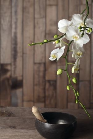 singing bowl: Fiori di orchidea bianca su uno sfondo scuro di legno close-up. La forma del telaio. Ciotola di canto Tibetian Archivio Fotografico