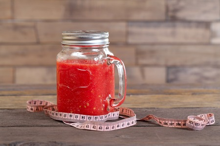 centimeter: Red smoothie and centimeter on old wood Stock Photo