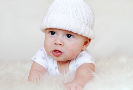 discontent: The angry baby in a white knitted cap  3,5 months