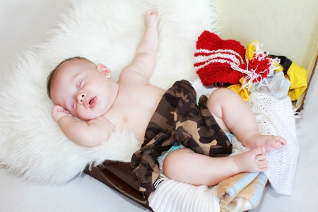 The baby sleeps in a suitcase with clothes  3,5 months   Stock Photo - 17420844
