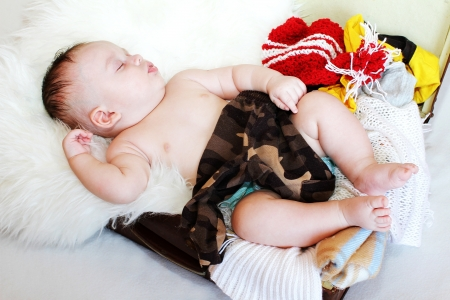 The nice baby sleeps in a suitcase with clothes  3,5 months Stock Photo - 17420771