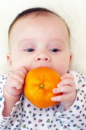 to be pleasant: The baby bites tangerine  3,5 months   Stock Photo
