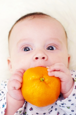 The surprised baby bites tangerine  3,5 months   Stock Photo - 17420827