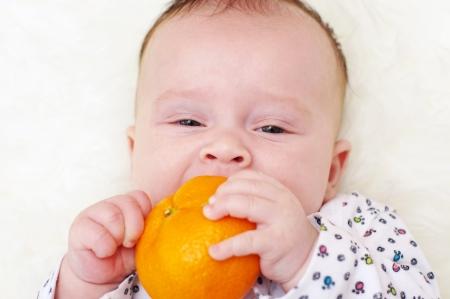 The baby bites tangerine  3,5 months Stock Photo - 17420908