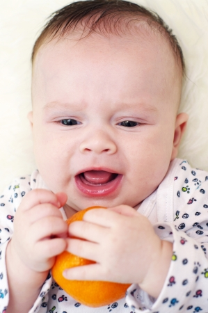 The whimsical baby doesn t want to give tangerine  3,5 months   Stock Photo - 17420841
