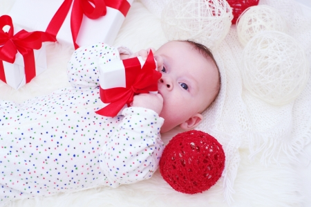 The baby lying with a gift in hands (3,5 months) Stock Photo - 17406032