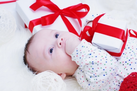 The four-months baby lies among gifts  Stock Photo