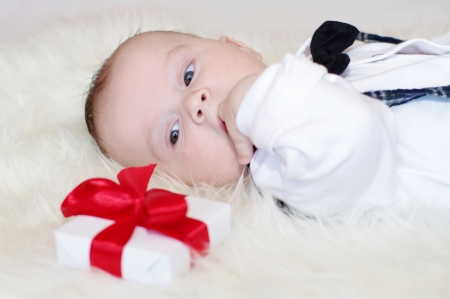 The baby looks at a gift lying nearby  photo