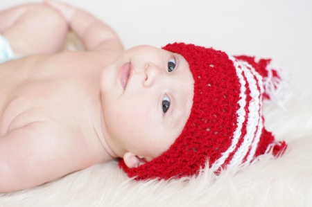 The amusing baby in a red knitted hat  photo