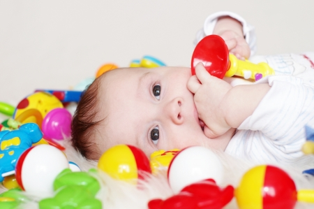 The four-months baby lies among toys Stock Photo - 17452047