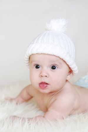 The surprised baby in a white knitted hat