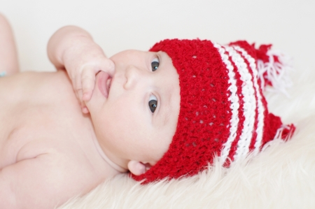 The amusing baby in a red knitted hat Stock Photo - 17452053