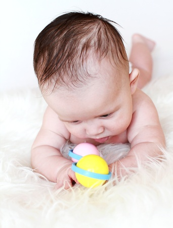 The baby lying on a stomach plays a rattle  3,5 months Stock Photo - 17567112