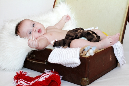 The happy baby lies in a suitcase with clothes  3,5 months Stock Photo - 17567115