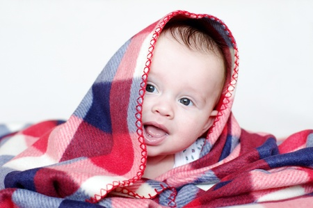 The four-months baby covered by a checkered plaid