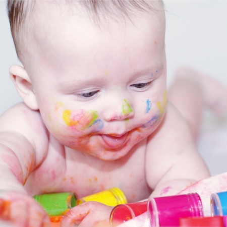 four hands: The baby draws finger-type paints  4 months   Stock Photo