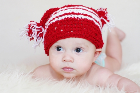 The amusing baby in a red knitted hat  Stock Photo