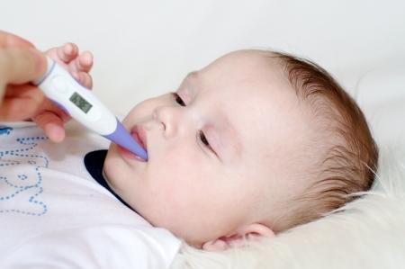bebe enfermo: El beb� toma la temperatura con un term�metro electr�nico Foto de archivo