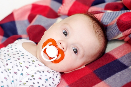 baby s: The baby with a baby s dummy lying on a checkered plaid